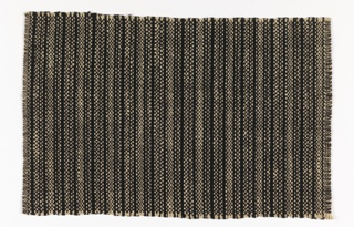 Uneven vertical stripe of black and tan.  The warp is of black cotton and heavy undyed bast fiber.  The black cotton wefts are interlaced singly with the black warp, but interlaced in pairs with the natural warp. The effect is of bands of dense black alternating with stripes of speckled black and tan.