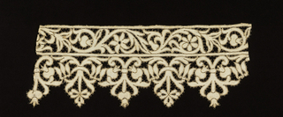 Border fragment with a serpentine floral motif edged with elaborate floral pendants. Pattern outlined by gold thread.