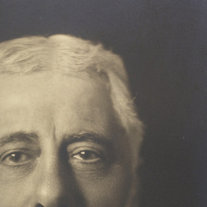 A photograph of Hector Guimard picturing him in a black suit against a black background showing him from the chest up.