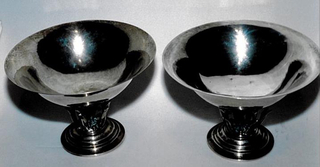 Circular stepped and domed foot supports circular bowl. Central support of upright grape cluster and three curled fronds, and outer supports of six leaf and scroll tendrils. Bowl is concave, plain hammered silver with flared and everted rim.