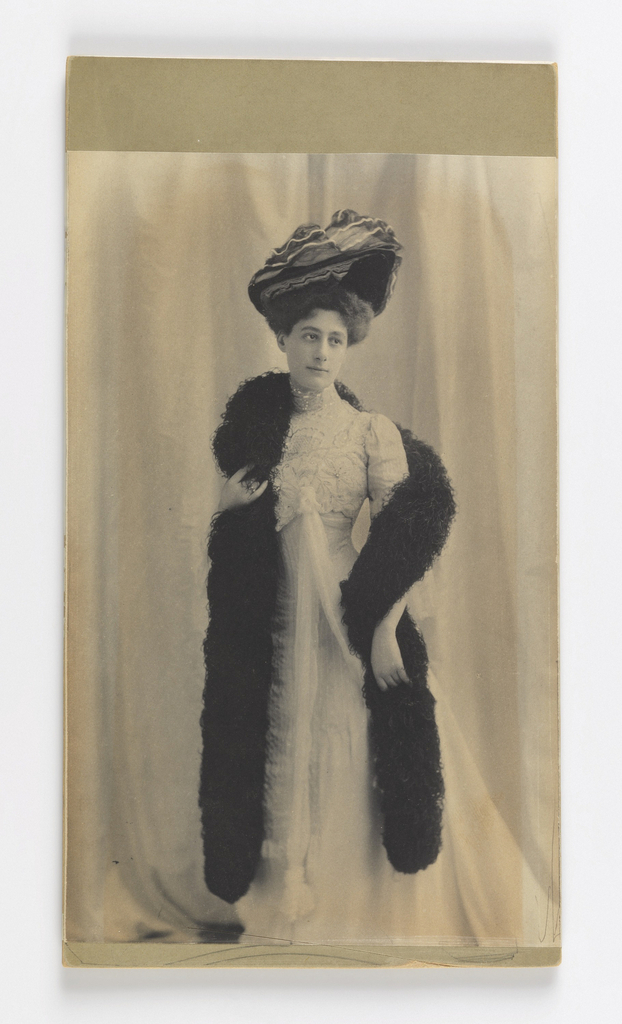 A full-length photograph of a woman dressed in late 19th to early 20th-century fashion. Set against a white background, she is wearing a white embroidered dress, a black boa and a large black hat.