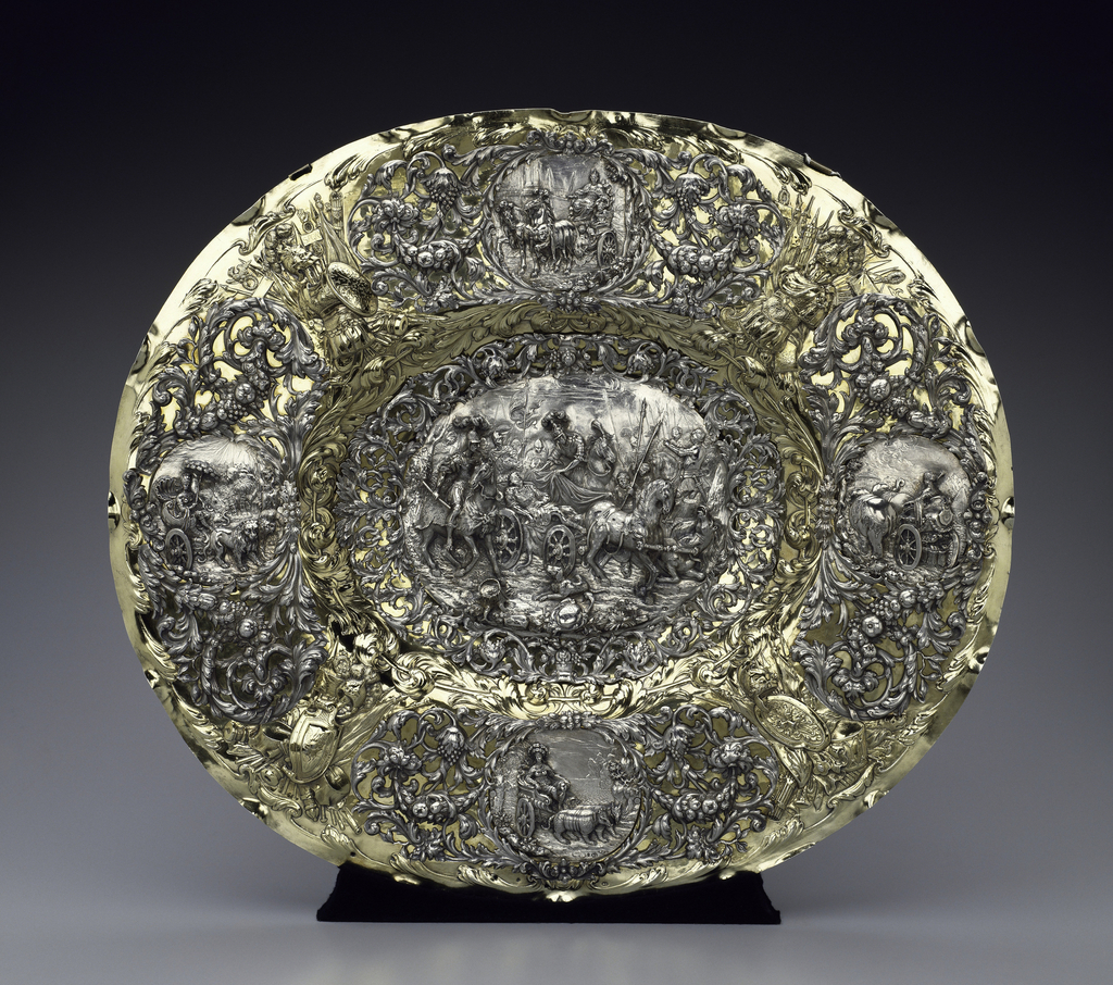 Oval, with four repoussé martial trophies on marli, wreath around center. Applied, on marli, four high relief medallions with the Four Continents (after Stefano della Bella's playing cards, published in Paris in 1646).  Asia, turbaned, in chariot drawn by two elephants; Europe, crowned, drawn by horses; Africa, with feather headdress and parasol, drawn by lions; America, in feather headdress and tunic, drawn by armadillos.  In center, relief plaque of Alexander and King Darius, lying dead in battle chariot with attending warriors (after an etching of 1645 by Hans Ulrich Frank).