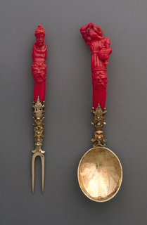 Two-tined fork with sloping shoulder; gilded neck elaborately decorated with leaves, masks and scrollwork; slightly curved handle of red coral, carved with a grotesque head on the front, surmounted by a torso and head of a man wearing a helmet; back of handle carved in decorative pattern. Spoon with oval bowl, gilded neck elaborately decorated with leaves, masks and scrollwork; slightly curving handle of red coral, carved with a grotesque head on the front, above the upper body of a woman holding a ewer in one hand and an urn in the other, as if pouring liquid from one into the other; back of handle has decorative pattern.
