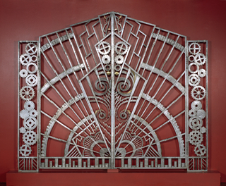 Pair of gates, each a mirror image of the other; gate -1 with handle.  Each gate with geometric decoration in two sections: a tall narrow rectangular section at outer left of gate -1, and outer right of -2, hinged to a larger trapezoidal section.  The narrow rectangular sections with decoration of 14 irregularly-stacked cogwheels. The trapezoidal sections with radiating arcs, lightning bolt-like forms and zigzag lines emanating from lower inside corners; cogwheels, spirals, and other shapes interspersed along inside edges; bottom edges with segmented border depicting stacks of coins.