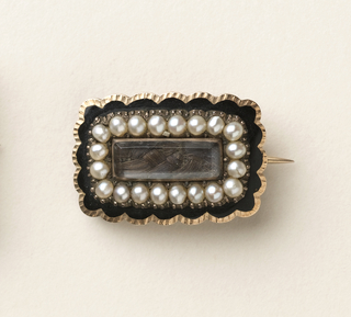 Small rectangle brooch with scalloped edges, a row of pearls, and a woven brown hair center.