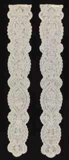 Mechlin-style bobbin lace lappets. Elaborate floral designs symmetrically arranged in a series of enframents of foliage. Deeply scalloped border at end.  Some Mechlin ground but mostly snowball ground.