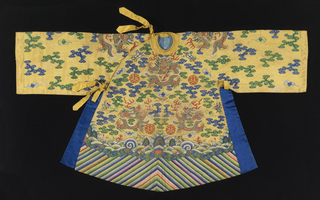 Small robe, possibly for a statue, with a tiny rounded neckline and asymmetrical closure, with yellow silk ties at the neck and side; side openings are edged with bright blue silk. In yellow silk tapestry weave, kesi, with metallic gold dragons on the front, back, shoulders and sleeves. The ground is filled with clouds motifs in blue and green; flaming pearls, bats, and other auspicious symbols. At the bottom is a deep wave border of multicolored diagonal stripes. 