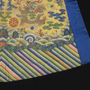 Small robe, possibly for a statue, with a tiny rounded neckline and asymmetrical closure, with yellow silk ties at the neck and side; side openings are edged with bright blue silk. In yellow silk tapestry weave, kesi, with metallic gold dragons on the front, back, shoulders and sleeves. The ground is filled with clouds motifs in blue and green; flaming pearls, bats, and other auspicious symbols. At the bottom is a deep wave border of multicolored diagonal stripes.  This small robe was most likely used to clothe a deity statue in a Daoist temple. The 5-clawed dragon and the bright yellow color were symbols of the Emperor of China, indicating that this robe was an imperial donation to a temple or used to clothe an image of a legendary emperor.