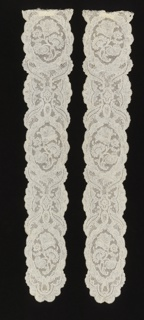 Cap streamers of Mechlin lace in a design showing repeated floral spray set within oval medallions, connected by a symmetric swirling and crossing leaf pattern, forming additional medallions containing centrally placed quatrefoil shapes.