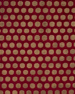 Deep red velvet with offset repeat pattern of gold disks. The foundation is plain weave formed by a red silk warp and tan silk weft; the supplementary warp pile is red silk. The velvet pile is voided in the areas where the coin dots appear, and supplementary gold wefts are floated in pairs to the surface in these areas, bound in twill with the secondary ivory warp.