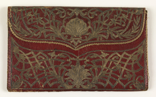 Red leather pocket book with ornamental panels and inscription within border. Remains of green silk lining.