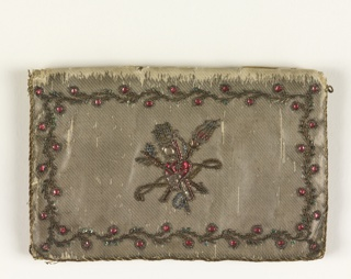 Silver cloth cover ornamented with vine borders worked in metal thread embroidery with spangles. Monogram C.F. on one side, heart with torches on the other.