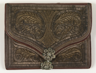 Envelope-shaped case with embroidery in conventionalized floral design and initials F.M., in couched silver thread on red leather. Pieces of leather divide interior into four pockets. Clasp of silver filigree.