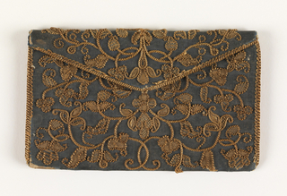 Letter case of blue silk taffeta embroidered with straw in a symmetrical floral design. Fiber is couched flat, twisted and braided. Worked as a single panel; lined with tan silk.
