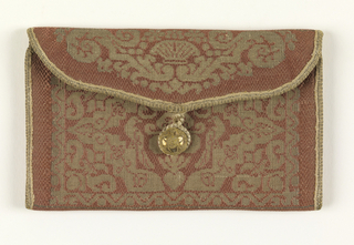 Small purse of deep rose silk with a pattern in greenish-white, shot with metal. Pattern is a symmetrical arrangement of a crown in the center with highly stylized vine forms. Same pattern front and back. Purse is an envelope shape with a silk loop and button to fasten. Blue taffeta lining.