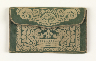 Small envelope-shaped purse in green and white silk. Pattern in white silk is a symmetrical arrangement of a crown with confronted dolphins and three fleurs-de-lis above with stylized foliage borders. Lined with pink taffeta.