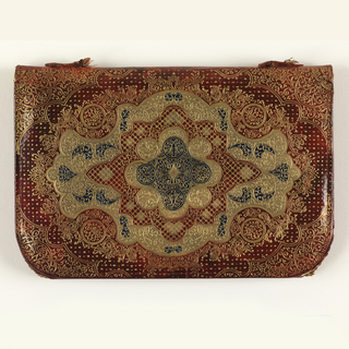 Small purse of stamped, tooled, and gilded leather purse with a geometric medallion in an oval framework, in blue and gold on a red ground. Back is plain red leather. Lined with maroon moiré silk.