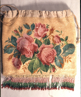 Bag knitted with colored glass beads with a spray of pink roses on a yellow ground. Tan silk at upper edge with silk cord drawstring; bead fringe at bottom in bands of pink, green and red.