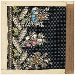Floral pattern embroidered in green and white silk, green and silver sequins, colored glass, and pink and blue foil on a black ground patterned with dots and dashes of blue and orange.