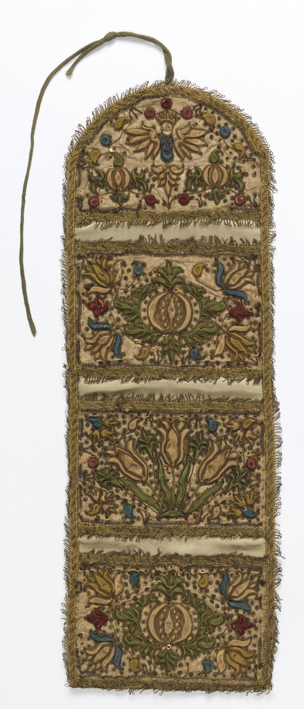 Wall pocket with three pockets and rounded top, made of dark green silk and decorated with floral designs of applied and padded silk in strong relief; outlined with gold thread and paillettes. Each pocket has a different design of symmetrical floral sprig in green, blue, red, and dark cream. At the top, a winged cherub with a painted face. Edged with fringed gold braid.