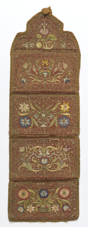 Wall pocket in red satin, embroidered in polychrome silks and metal threads. Four pockets and a shaped top, each decorated with flowers, worked in satin stitch and shaded, and outlined with metal thread and with couched metal thread for foliage. Fruit, wheat, and birds also feature in the design. Edged with gold lace, bound with linen tape and backed with red brocatelle.