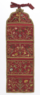 Long wall pocket with four sections and shaped top, made to hang. Bright red satin with embroidery in colored silks and metal threads. Each section has a symmetrical vine and flower design worked in polychrome silks, with gold threads, cords, and raised work. Trimmed with gold braid; backed with red taffeta.