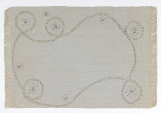 Grey place mat with meandering embroidery of swirls and starbursts. Fringe on right and left ends.