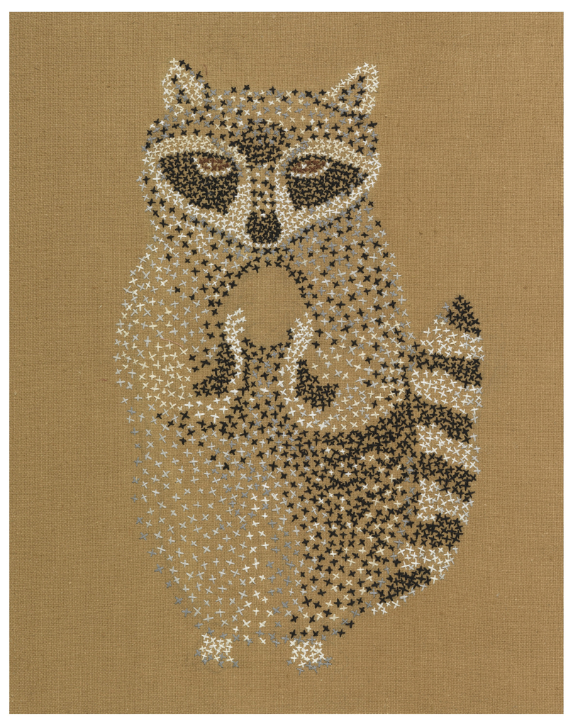 A sinister-looking raccoon standing with forepaws raised as if holding an empty space (unfinished?); worked in uncounted cross stitches in white, grey-blue, brown and black on light brown cotton ground.