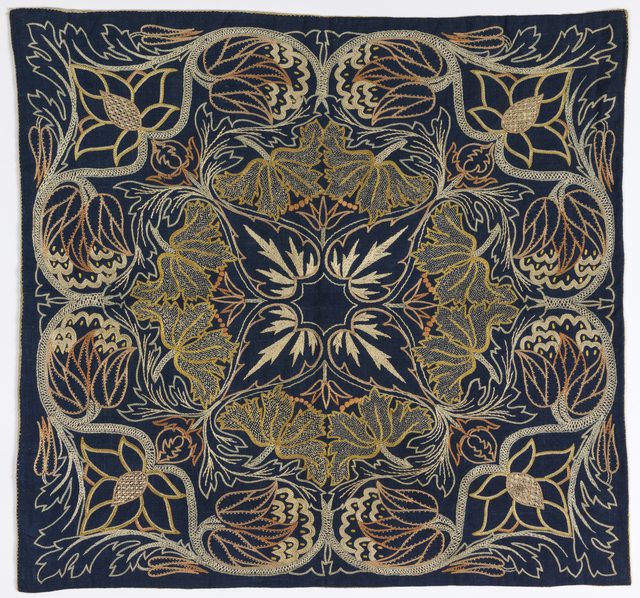 Silk embroidery in pale colors on dark blue linen. A horizontally and vertically symmetrical floral pattern in the Morris style.