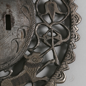 Circular lock with openwork border depicting tulips, lions, and possibly monkeys. Mask at the bottom. Pair with -134