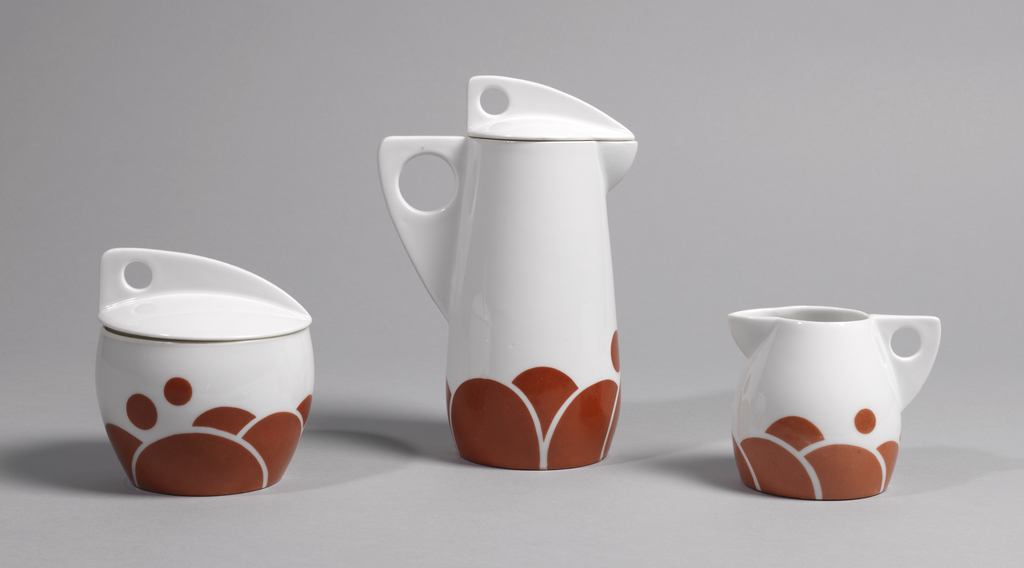 Five-piece coffee set includes covered sugar bowl, milk jug, cup and saucer, and plate. Coffee Pot (-1a,b): tall slightly conical form with broad, flat triangular handle with circular opening; small curved triangular spout; white ground overall, the bottom decorated with various sized circles in brown, some overlapping; white lid with large flat triangular handle with pierced circle at back. Sugar bowl (-2a,b): circular bowl (a) tapering toward base; white ground overall, the bottom decorated with various sized circles, some overlapping; slightly domed white lid with large flat triangular handle with pierced circle at back. Cream jug (-3): White porcelain ovoid form, tapered toward flat circular base; broad, flat triangular handle pierced with circular opening; curved triangular spout; white ground overall, the bottom decorated with various sized circles, some overlapping. Cup and saucer (-4a,b): circular cup (a) tapering toward flat base; curved flat triangular handle on side, pierced with circle; white body, the lower portion enamelled with red-orange semi-circles and dots arranged in asymmetrical pattern. Circular saucer (b) with slightly upturned edge; cup recess molded off-center; surface enamelled with red-orange dots and overlapping semi-circles clustered around cup recess. Plate (-5): circular form with slightly upturned edge; white ground overall, the surface enamelled with scattered red-orange dots and clusters of overlapping semi-circles.