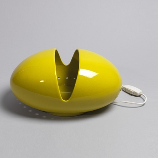 Yellow, horizontal ovoid form with short circular base; V-shaped opening at center, exposing lighting element; series of small circular holes in body immediately above base.