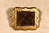 Rectangular brooch. Center of woven bundles of brown hair enclosed behind glass. Frame border of gold with scalloped edge; surface of frame engravedwith foliate scrolls. Reverse plain gold. Simple single pin and catch closure.