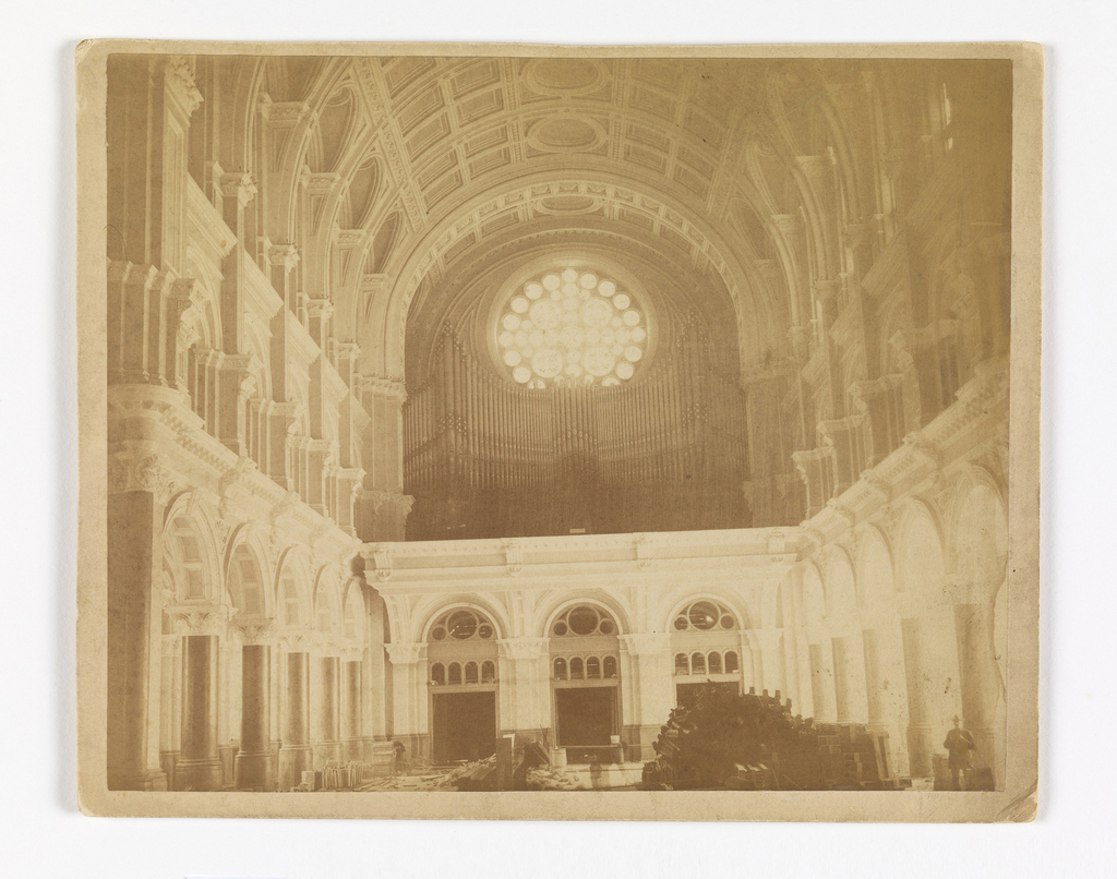View looking west, showing the rose window after Dabo's design, behind the gallery organ, over the main entrance. Flooring unfinished. Man stands at lower right.