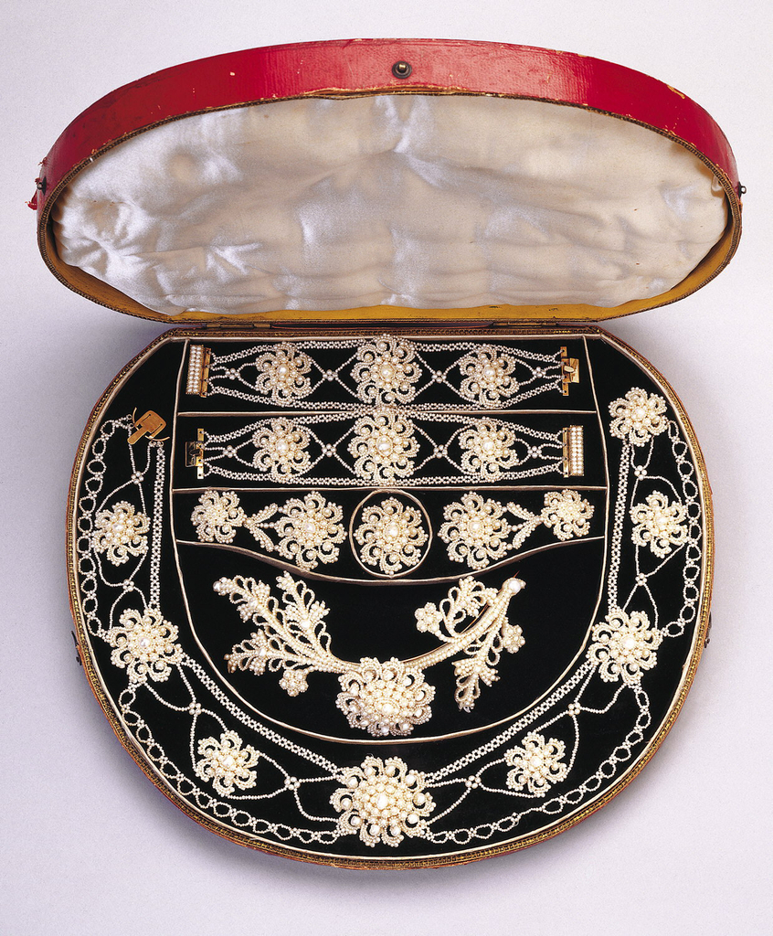 Hair ornament of woven pearls making flowers in a row. Hair ornament and companion members of suite in a circular red leather case designed to hold the group.