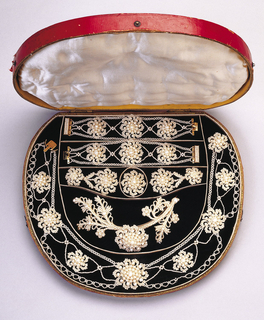 Parure composed of seed pearl necklace, brooch, hair ornament, bracelet, and earrings showing sunburst and floral ornaments within seed pearl strands, loops and foliate forms; gold clasps on necklace and bracelet.  All in a circular red leather case designed to hold the group.