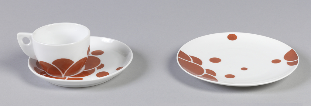 Circular plate with slightly upturned edge; white ground overall, the surface enamelled with scattered red-orange dots and clusters of overlapping semi-circles. Part of a set that includes a covered sugar bowl, milk jug, cup and saucer, and plate.