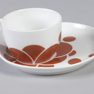 Circular cup (a) tapering toward flat base; curved flat triangular handle on side, pierced with circle; white body, the lower portion enamelled with red-orange semi-circles and dots arranged in asymmetrical pattern. Circular saucer (b) with slightly upturned edge; cup recess molded off-center; surface enamelled with red-orange dots and overlapping semi-circles clustered around cup recess. Part of a set that includes a covered sugar bowl, milk jug, cup and saucer, and plate.