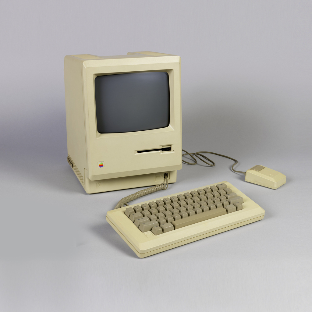 Beige rectangular computer (a)  with glass screen above computer with glass screen and floppy disc drive, plastic keyboard and mouse with connecting wires.