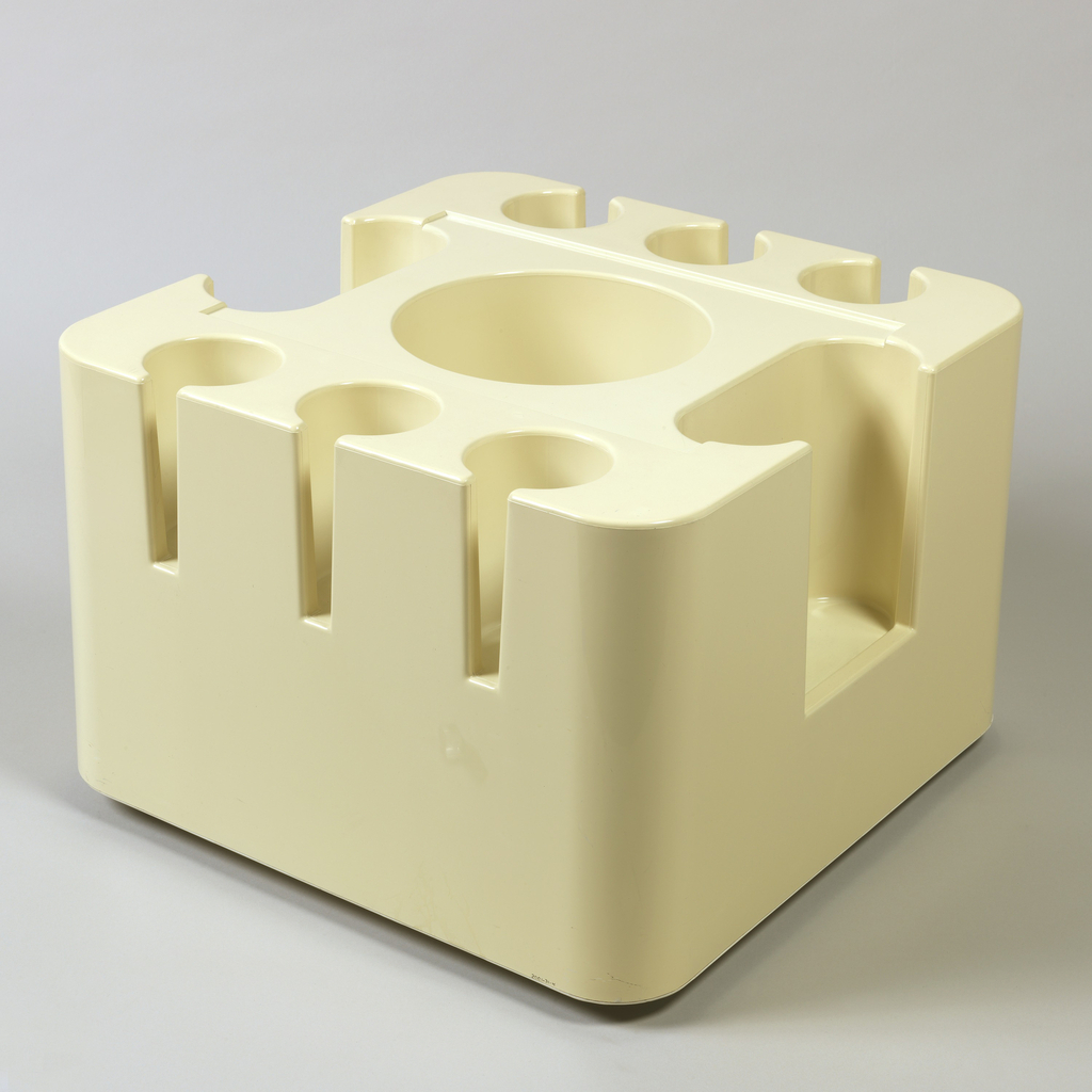 Molded cube shape of off-white plastic, casters; large cylindrical well in center, three smaller wells on two sides, one oval well on each of other two sides.