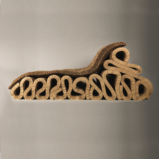 Base consisting of a continuous, ribbon-like curved mass of layered corrogated cardboard topped by a separate horizontal corrogated cardboard sheet acting as a cushion.