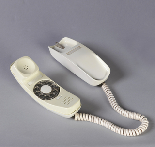 White ovoid body consisting of handset on base; coiled white cord at one end; rotary dial on underside of handset.
