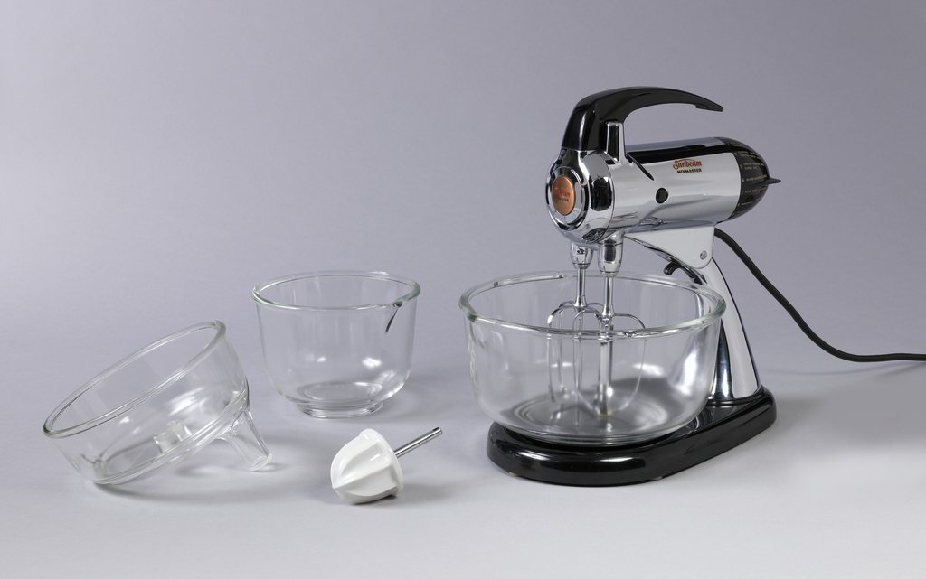 """One-piece, metal and plastic mixer stand (a) composed of cylindrical, metal motor unit with plastic handle at top and settings dial on rear, atop a curved metal arm on a tear-drop shaped plastic base with name on side: """"Sunbeam / MIXMASTER""""; circular plastic turntable (b) inset in base, to support one of two interchangeable bowls: small circular clear glass bowl (c); large circular clear glass bowl (d).  Motor unit tilts back, allowing removal of bowl, and access to two detachable metal beaters (e,f) descending from unit.  Additional interchangeable components are: white ceramic reamer on metal shaft (g); clear glass juicer (h) in form of shallow, circular bowl with tube-like protrusion."""