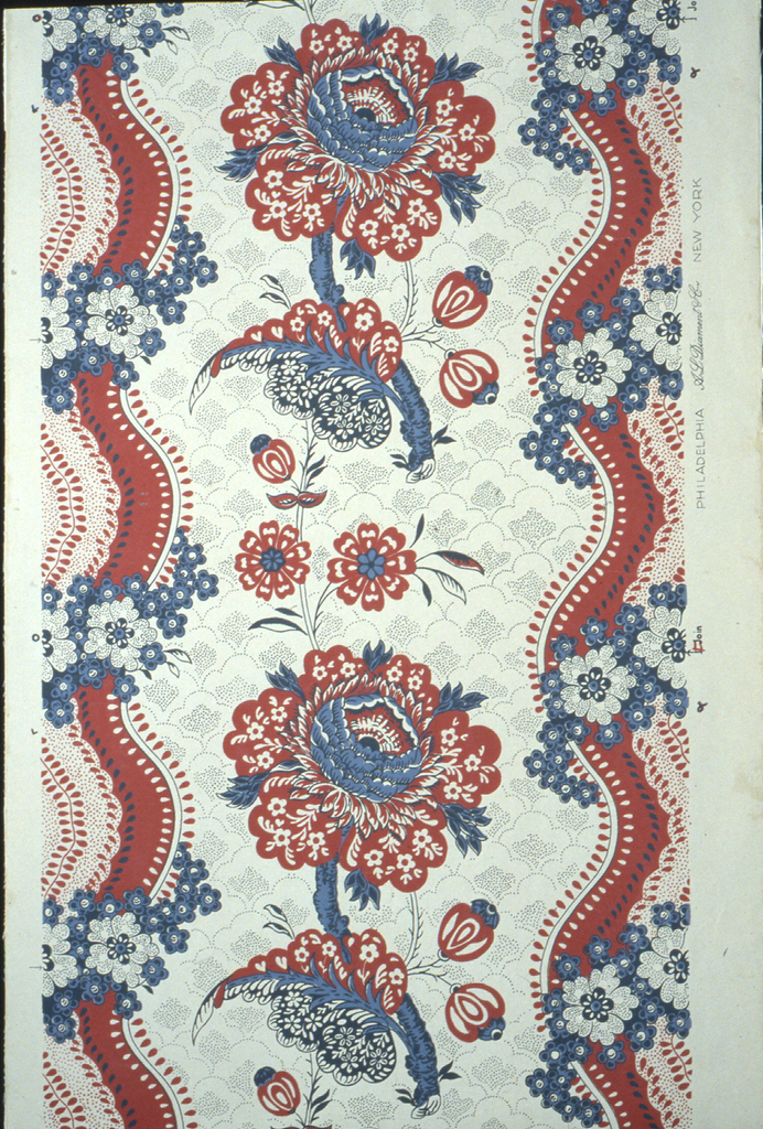 """A reproduction of a French toile of the late 18th century. A large flower with leaf and small sprays suggestive of floral designs on prints from India is the center drop repeat. The field is covered in a small design in picotage. A serpentine ribbon with a lace effect in center runs along both margins with a floral chain twined around. Printed in margin: """"A.L. Diament"""". Printed in red and blue on putty-gray ground."""