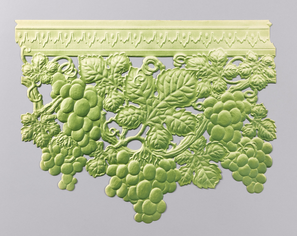 Clusters of grapes hanging from vines. Vines are suspended from architectural molding. Printed in green. This border section is one full repeat and fits together along the top edge much like pieces of a puzzle.
