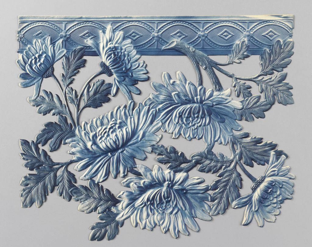 Floral motif, possibly daisies or mums, suspended from guilloche band at top edge. Printed in blue. This border section is one full repeat and the top edge fits together much like the pieces of a puzzle.