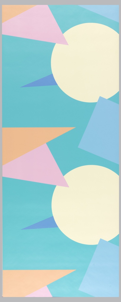 Large-scale, bold geometric shapes in repeating design. The circular, triangular and rectangular shapes all extend beyond the edge of the paper. Printed in tan, pink, orange and blue on a turquoise ground.