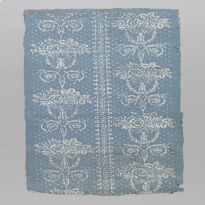 Floral bouquets, with foliate swags and scrolls, printed in white on blue ground. A lacey white stripe runs vertically through the center of the paper.