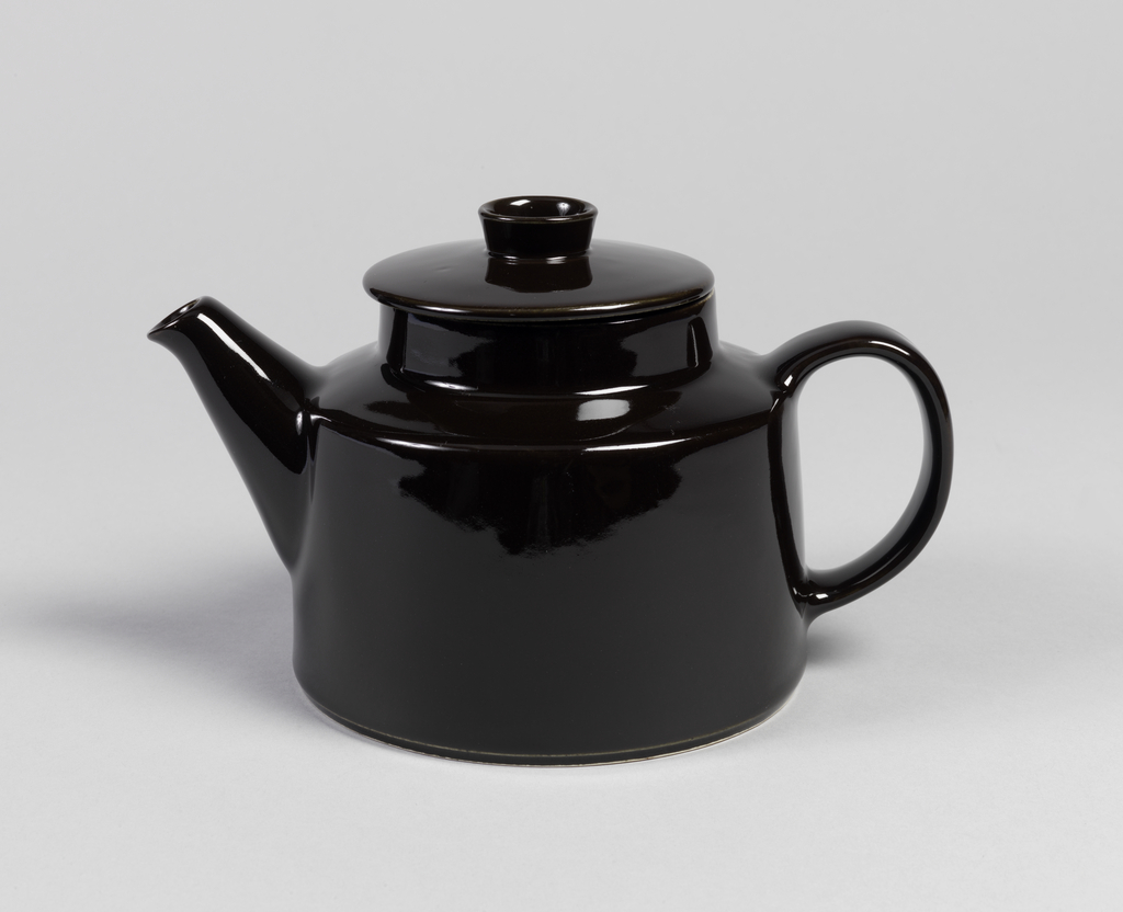 """Molded cylindrical body (a); flat base, straight sides. Tapered applied spout, """"c"""" shaped strap handle. Shoulder angled, with central collared neck. Slightly domed cover (b) with recessed flange, circular finial with concave center. Overall black gloss glaze; unglazed foot ring underside."""