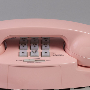 Pink telephone with oval body, handset cradled horizontally across top, above white keypad with black numerals; pink coiled cord on left connecting handset to body.